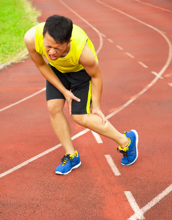 cramp: young male runner suffering from leg cramp on the track in the stadium Stock Photo