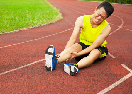 sore muscles: young male runner suffering from leg cramp on the track in the stadium Stock Photo