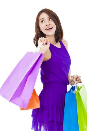 mujeres elegantes: Mujer joven asi�tica de la celebraci�n de la bolsa de compras sonriente sobre fondo blanco