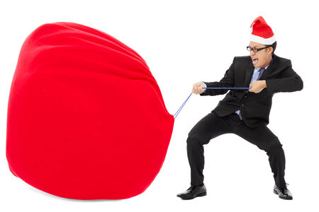 business man carrying a heavy gift sack with christmas hat. isolated on white background photo