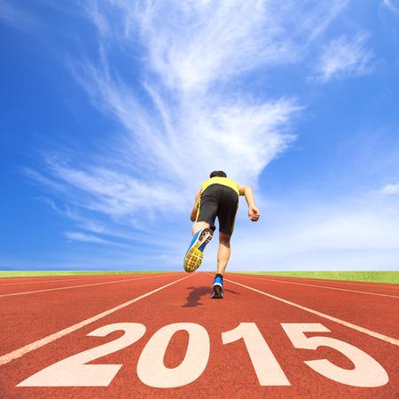 nouvel an: heureuse nouvelle ann�e 2015. jeune homme courant sur la bonne voie avec le ciel bleu et de nuages ??fond Banque d'images