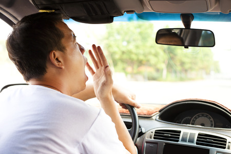 Exhausted driver yawning and driving car on the road Stock Photo