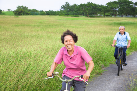 Happy asian seniors couple biking in the park.retirement and healthy lifestyle concept photo