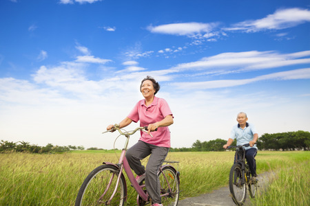 Happy Asian elderly seniors couple biking in farm with blue sky background photo