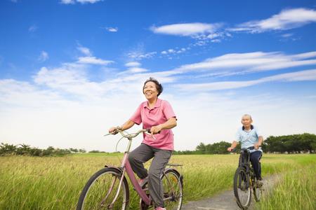 ancianos felices: Personas mayores de edad asiática joven en bicicleta feliz en la granja con el fondo del cielo azul