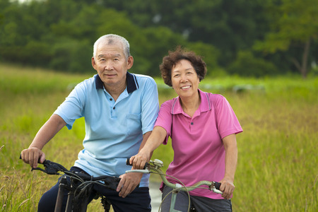 Happy Asian seniors couple biking in Park. retirement and health concept