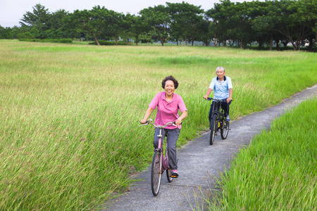 Happy asian seniors couple biking in the park.retirement and healthy lifestyle concept