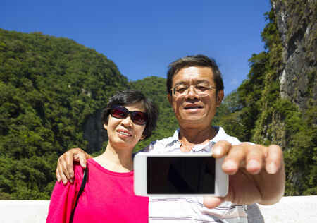 senior asian: Senior couple taking picture of themselves outside with mountain background