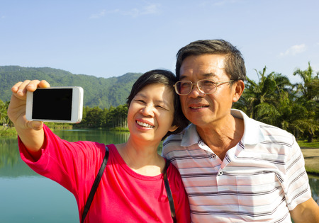 Senior couple taking picture by themselves outside with lake background photo