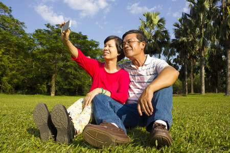 senior asian: Asian Senior couple sitting on grassland and  taking picture by themselves outside