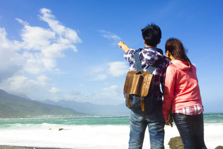rear view of young couple looking and pointing to sky photo