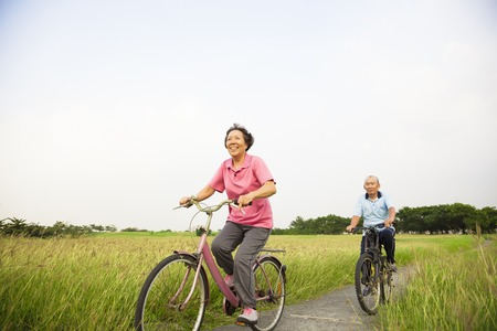 Happy Asian elderly seniors couple biking in the park