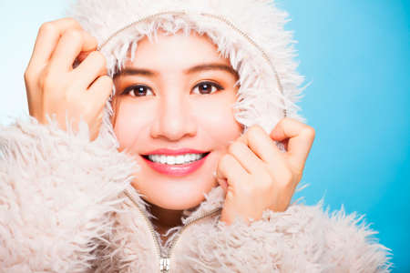 smiling asian girl with winter wear sweater.