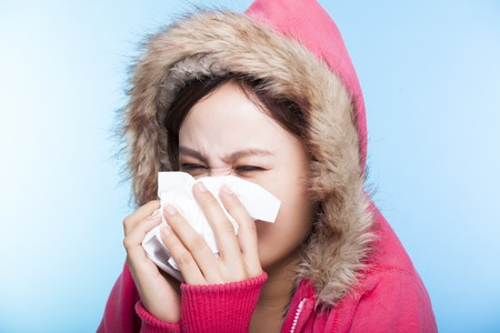 overcoat: young Woman catch a cold and sneezing nose with a sweater. Stock Photo