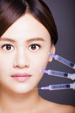 asian beautiful woman gets injection in her face. photo