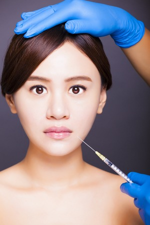 asian beautiful woman gets injection into her mouth photo