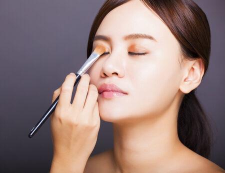 Make up artist applying  color eyeshadow on model 免版税图像