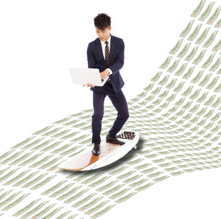 business man holding a laptop and surfing on the money wave . photo