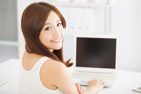 usando computadora: feliz joven mujer asiática con un ordenador portátil en casa