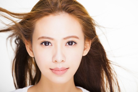 beautiful young woman face with hair motion on white background. skin care and hair salon concept.