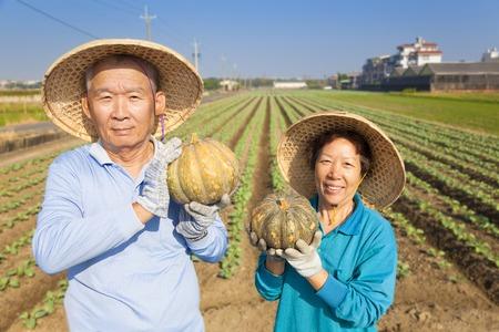 asian produce: asian senior couple farmer holding pumpkin on his farm Stock Photo