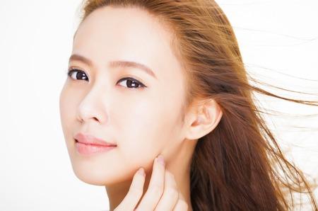 髪の動きと美しい若い女性の顔。皮膚のケアと髪サロン コンセプト 写真素材