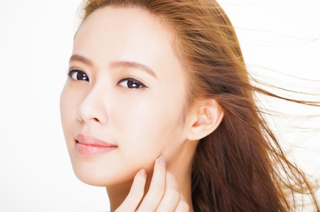 beautiful young woman face with hair motion . skin care and hair salon concept. Standard-Bild