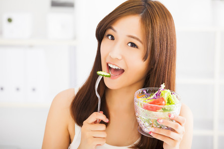 woman eating fruit: smiling young woman eating fruits and salad. healthy eating concept