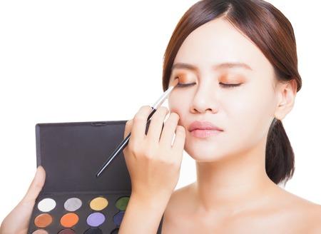 Makeup artist applying colorful eyeshadow on model photo