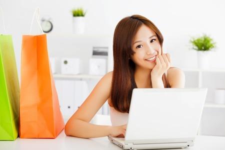 usando computadora: feliz mujer asiática joven con un ordenador portátil con bolsas. tiendas en el concepto de línea Foto de archivo