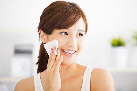 mujer alegre: Joven y bella mujer asi�tica limpieza de la cara con algod�n Foto de archivo