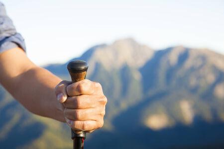 hand holding alpenstock and  mountain peak background photo