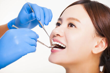 examined: Close up of female patient having  teeth examined by dentist