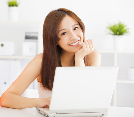 Young smiling asian woman  with laptop Фото со стока