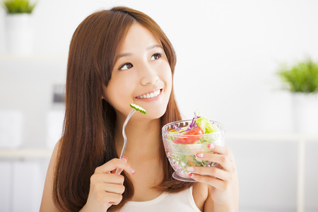 beautiful girl eating healthy food salad