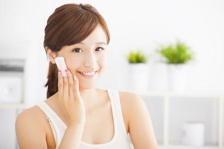 Mooie Aziatische jonge vrouw het reinigen van haar gezicht met katoenen