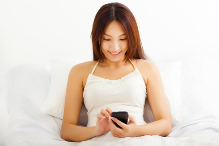 Happy young woman lying on bed using her smart phone in her bedroom photo