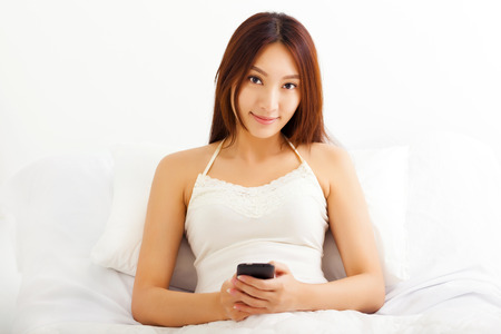 young woman lying on bed using her smart phone in her bedroom photo