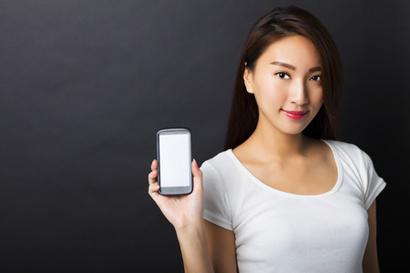 showing: beautiful young woman showing smart phone with black background