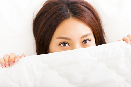 hide: young smiling woman in bed Stock Photo