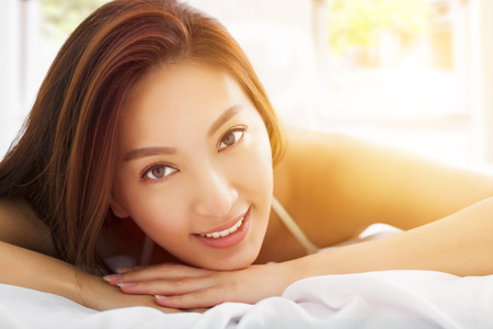 young Beautiful asian woman relaxing on the bed with sunlight background
