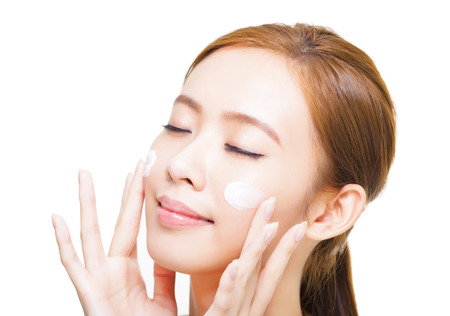 happy faces: beautiful young woman applying cosmetic cream  on her face