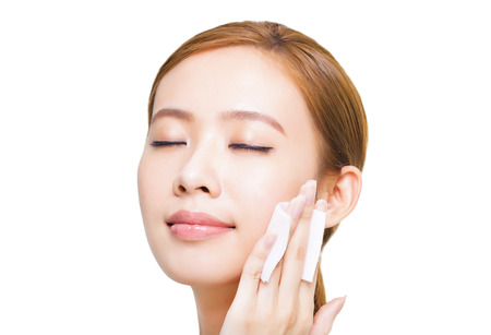 Mooie jonge vrouw het reinigen van haar gezicht met katoenen
