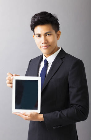young smiling business man showing tablet pc photo