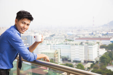 relaxed businessman watching the city view photo