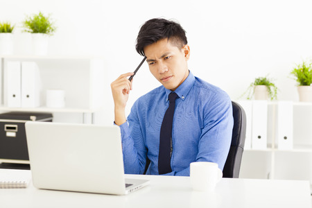 männchen: Junger Geschäftsmann beobachten Laptop und Denken