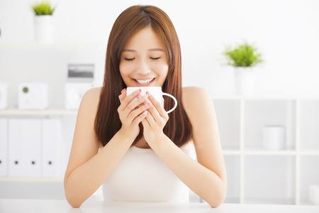 mujer tomando cafe: feliz asiático joven bebiendo café