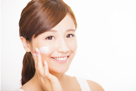 asian girl face: beautiful young woman applying cosmetic cream  on her face