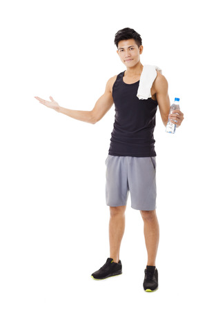 man drinking water: Full length  of smiling  young  man  showing Stock Photo