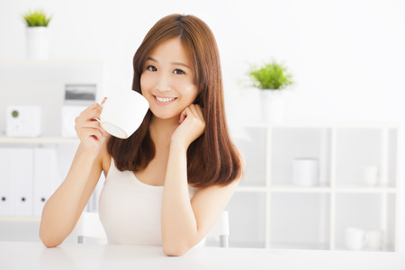 women holding cup: happy asian young drinking coffee Stock Photo